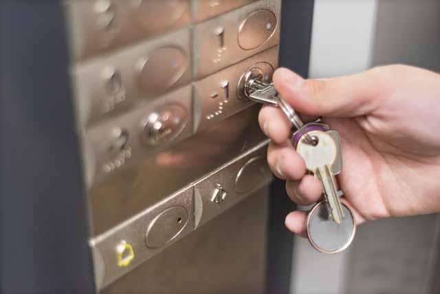 Fotografía de persona accionando con llave el acceso a planta -1 en un ascensor.