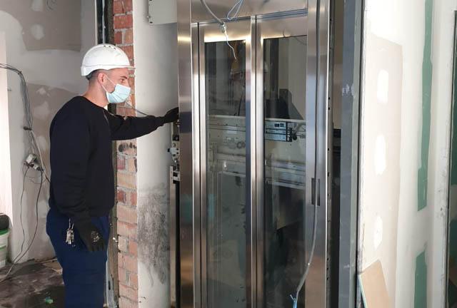 Técnico de Ascensores Domingo instalando una puerta de cristal en un ascensor.