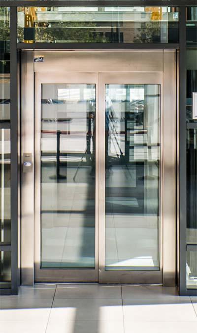 Puerta de ascensor automática en acero y gran ventana.
